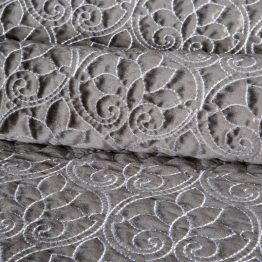 Silver quilted bedspread with floral design